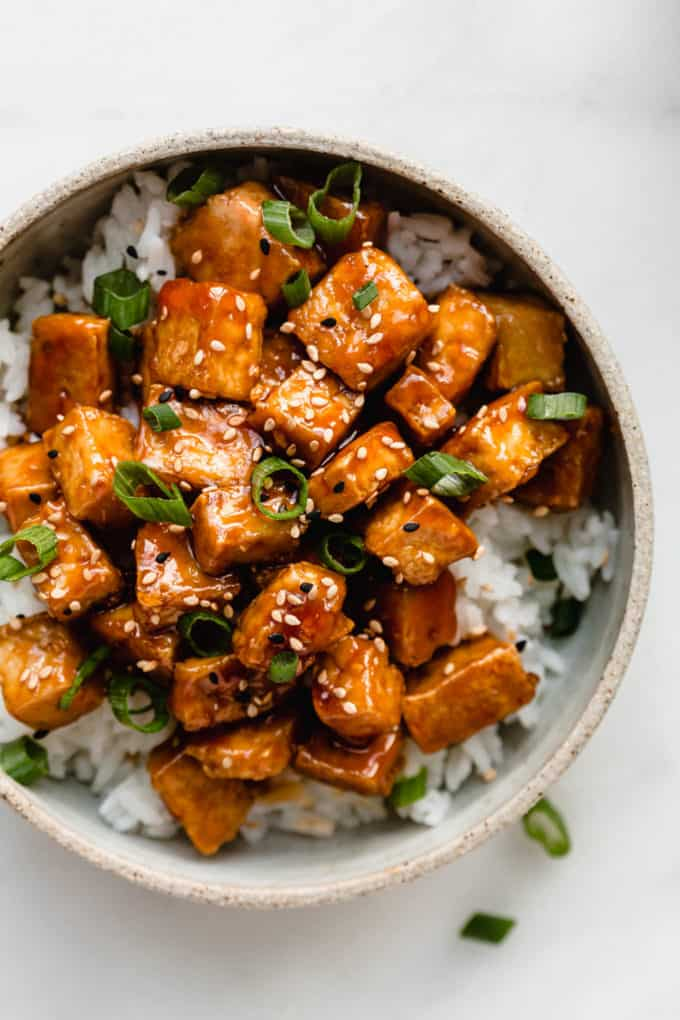 A bowl filled with rice and sweet and sour tofu topped with sliced green onions