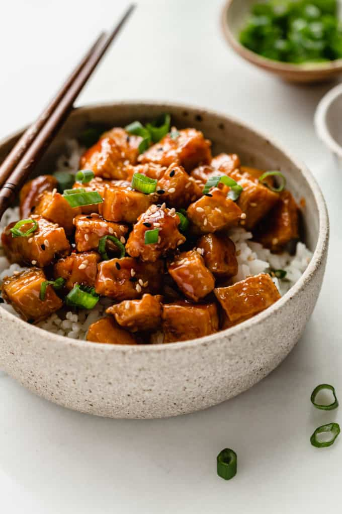 A ceramic bowl with asian tofu in it with a small bowl of green onions in the back