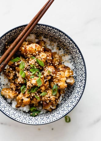 kung pao cauliflower topped with green onions and sesame seeds