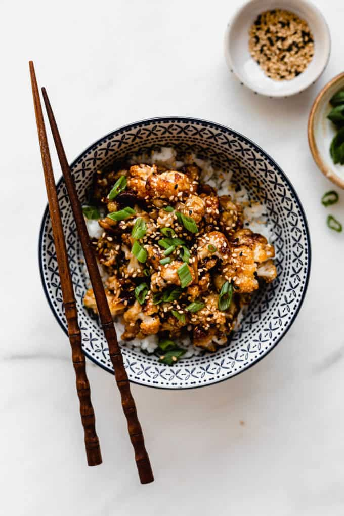 roasted cauliflower in a blue bowl topped with green onions and wood chopsticks