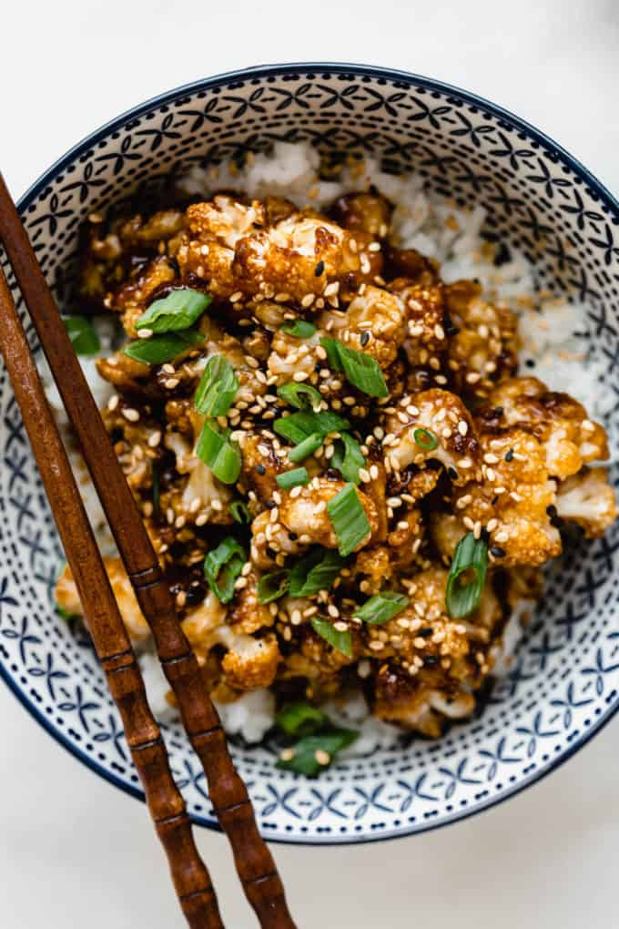 roasted cauliflower with sauce topped with green onions in a blue bowl