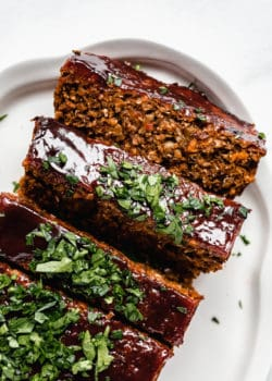 lentil loaf sliced on a white serving platter topped with chopped parsley