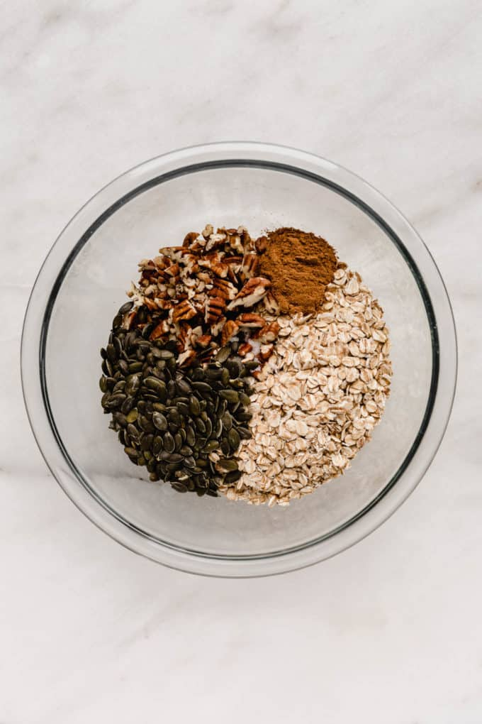 A mixing bowl of oats, pumpkin seeds and pecans