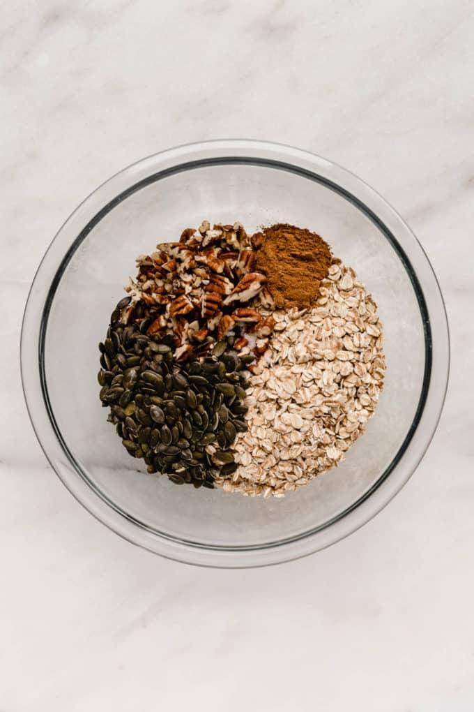 A mixing bowl of oats, pumpkin seeds and pecans