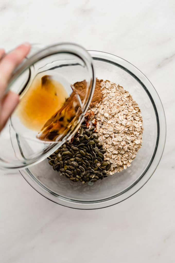 a hand pouring maple syrup into a bowl of oats, pumpkin seeds and pecans