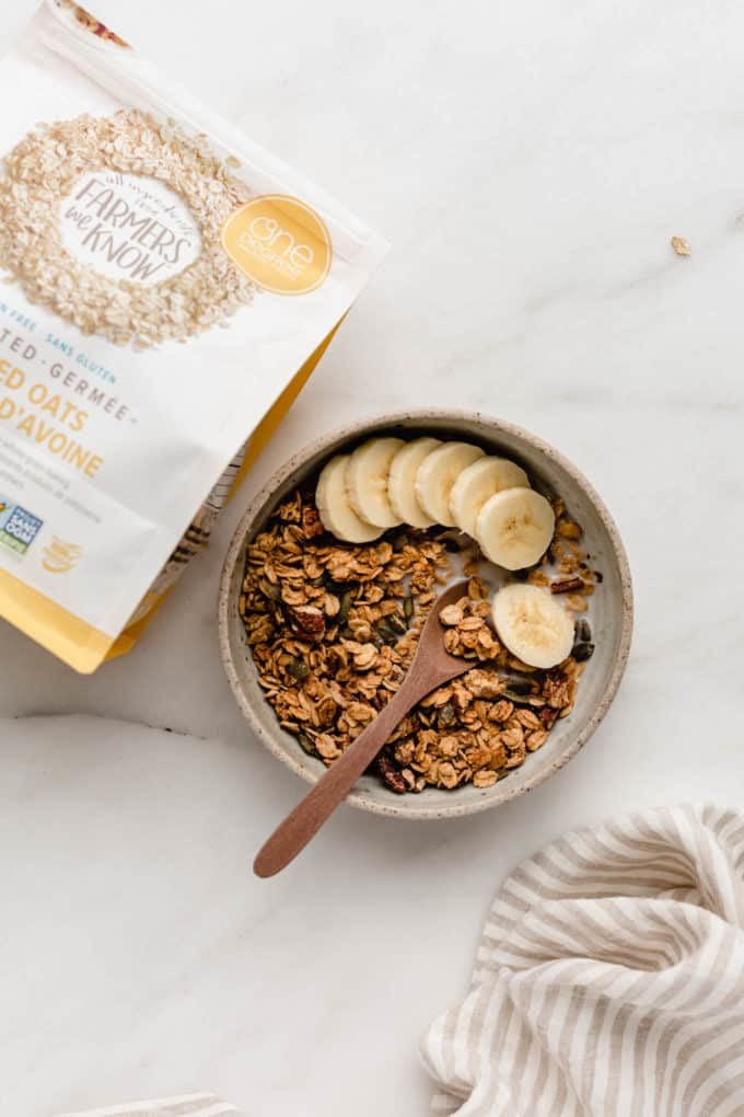 A bowl of granola with bananas in it and a package of oats on the side