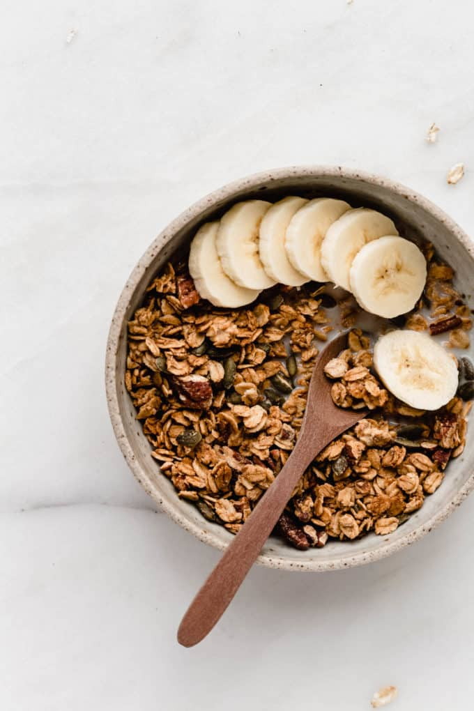 A bowl of pumpkin spice granola with sliced bananas in it
