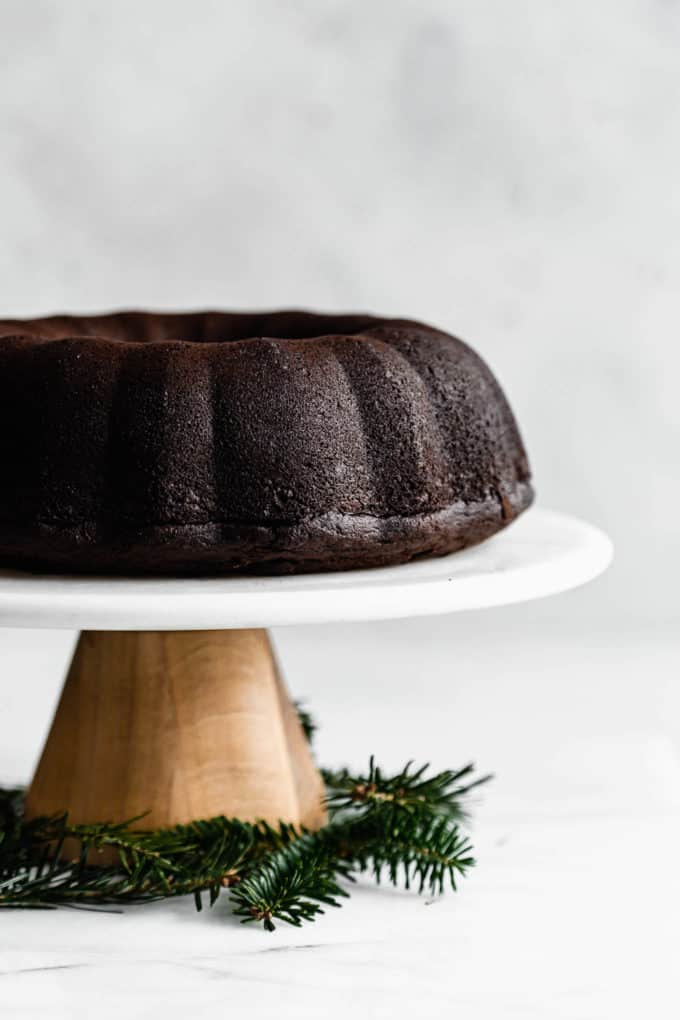 A wooden and marble cake stand with a gingerbread bundt cake on it