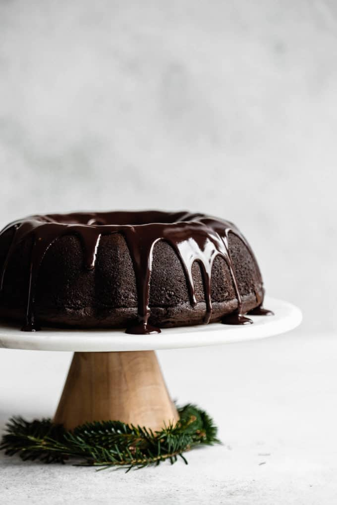 A gingerbread bundt cake topped with chocolate glaze on a marble and wooden cake stand