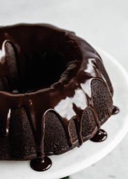 A close up of a gingerbread bundt cake with chocolate glaze dripping down the sides