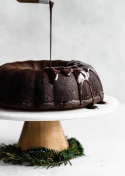 A gingerbread bundt cake on a marble cake stand with chocolate glaze being poured onto it