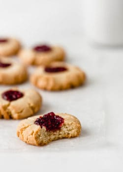 A vegan raspberry thumbprint cookie with a bite taken out of it on a marble counter