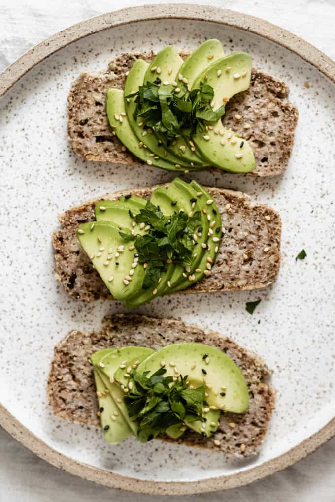 three slices of avocado toast on buckwheat bread on a white ceramic plate