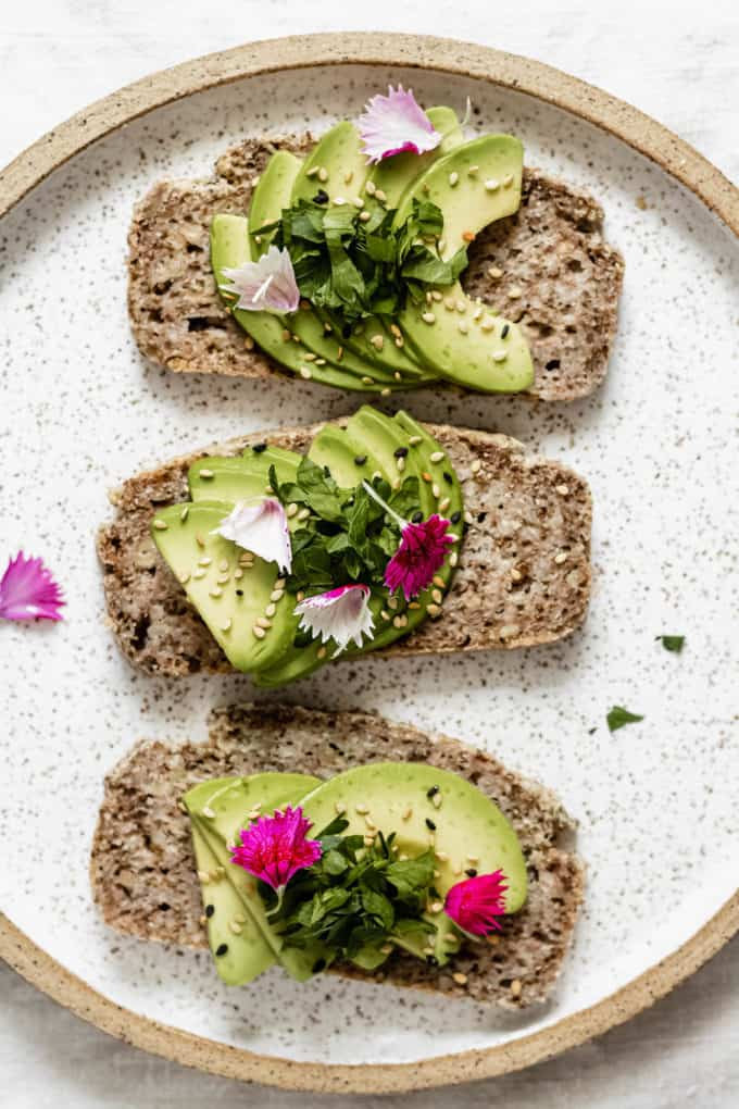 three slices of avocado toast on a plate topped with pink flower petals