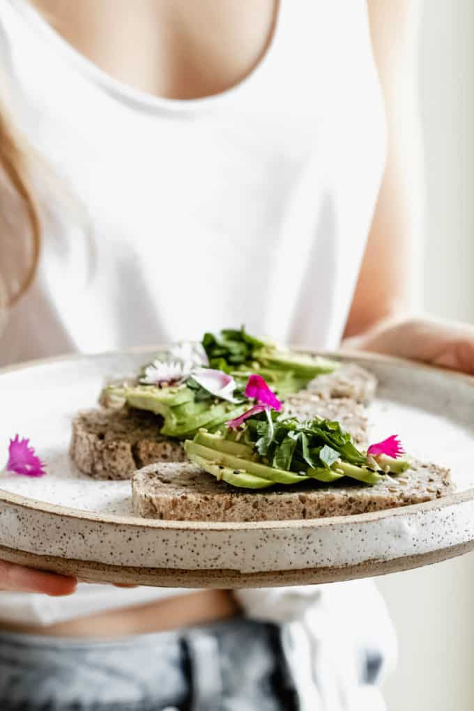 a person holding a white plate with avocado toast on it topped with flower petals