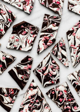peppermint bark broken up on a marble tray with crushed candy canes on top