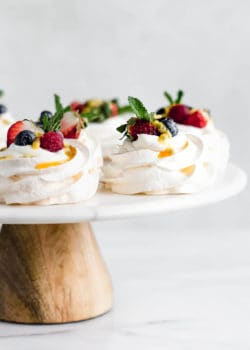 mini pavlovas on a marble and wood cake stand