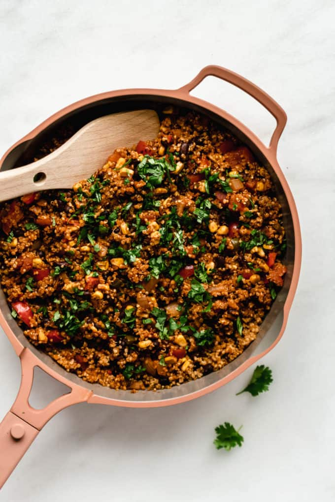 A pan of Mexican quinoa with a wooden spoon in it topped with cilantro