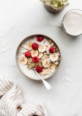 A breakfast quinoa bowl topped with bananas and berries with a glass of milk and flowers on the side