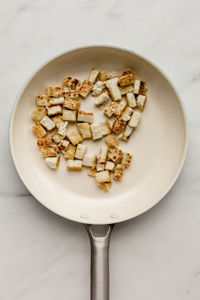 A white pan with cubes of tofu in it