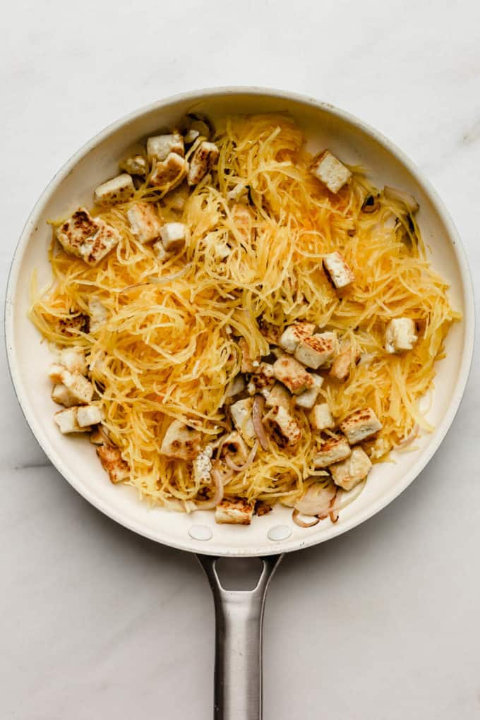 A white pan with spaghetti squash and tofu in it
