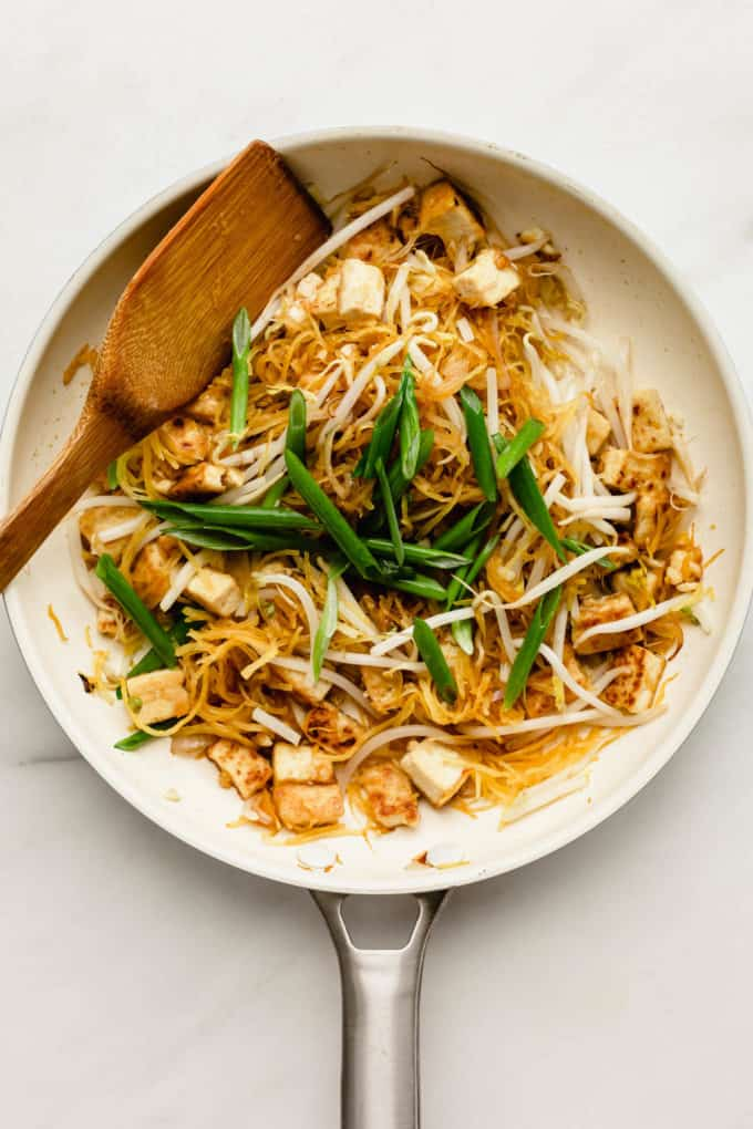 Spaghetti squash, tofu and green onions in a white pan