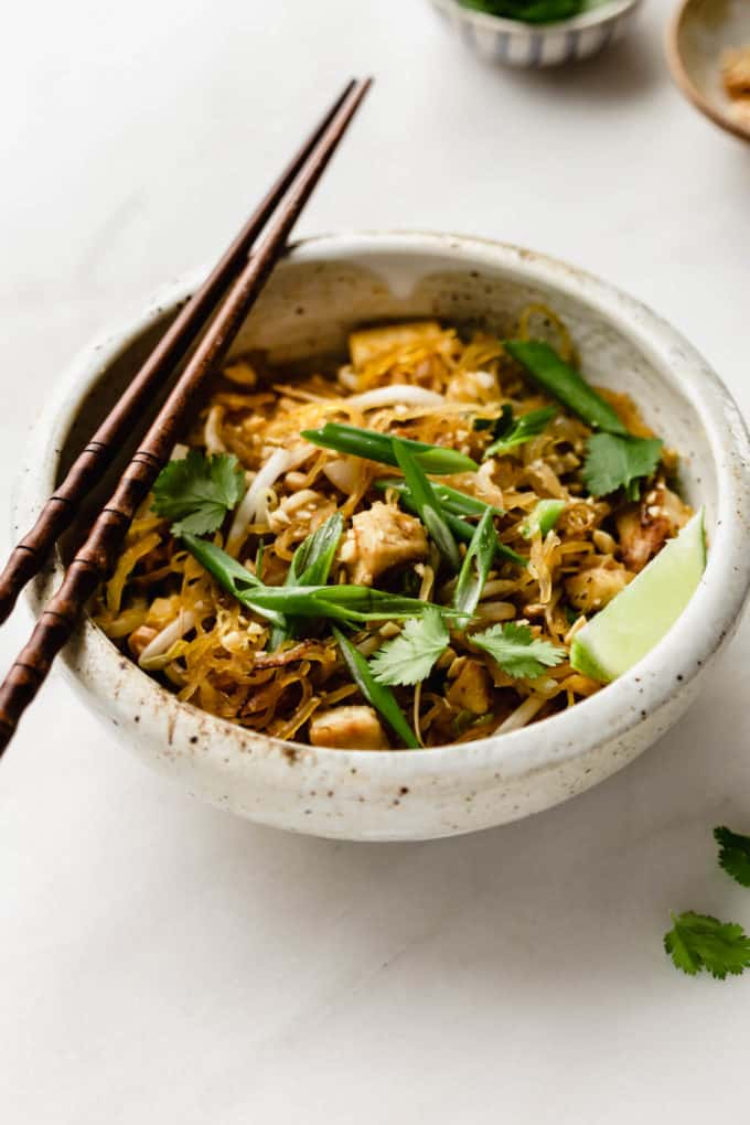 A bowl of spaghetti squash pad thai topped with sliced green onions