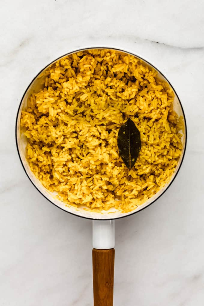 A white pot with turmeric rice and a bay leaf in it