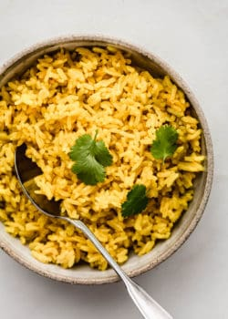 A bowl of turmeric rice topped with cilantro