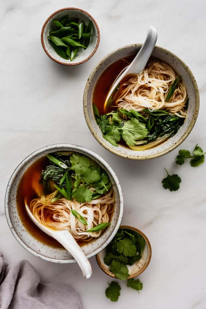 two bowls of pho soup with noodles and bok choy in them