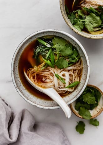 A bowl of vegan pho soup with rice noodles, cilantro and green onions