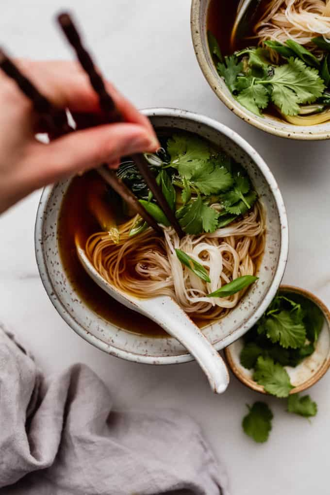 A bowl of vegan pho with chopsticks in it