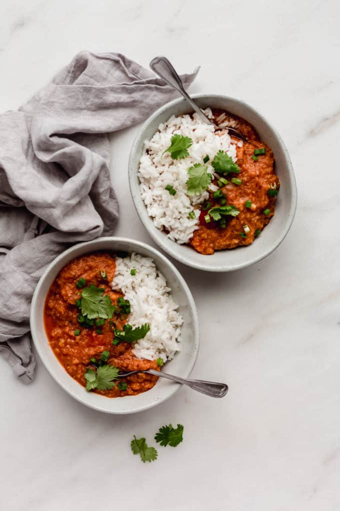 two bowls of red lentil curry and rice with spoons in them and a grey napkin on the side