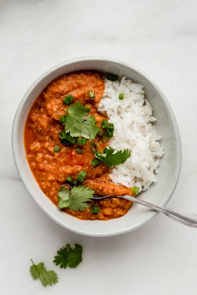 A bowl with rice and lentil curry in it