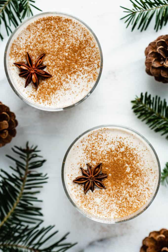 A topdown view of two glasses of vegan eggnog on a white counter with pine leaves around them