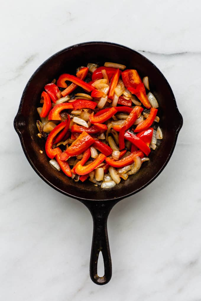 A cast iron skillet with sliced peppers and onions in it
