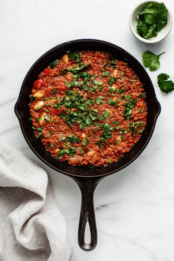 A vegan shakshuka in a cast iron skillet topped with parsly and a napkin and parsley on the side