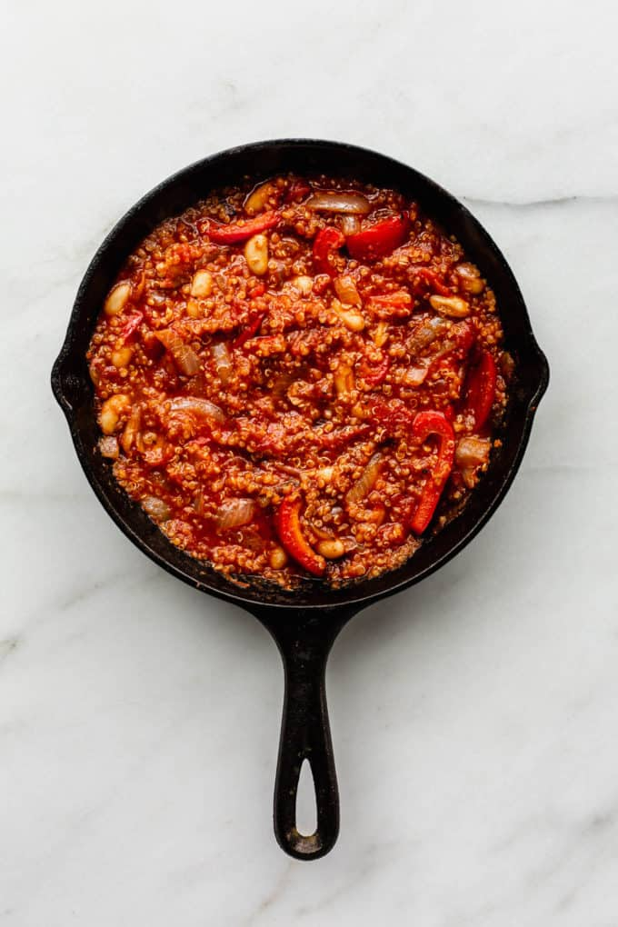 Quinoa, crushed tomatoes, red peppers and white beans in a cast iron skillet