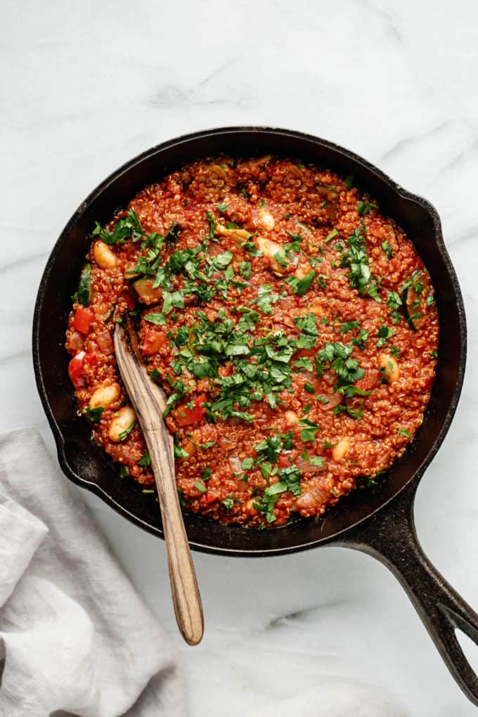 A vegan quinoa shakshuka with a wooden spoon in it