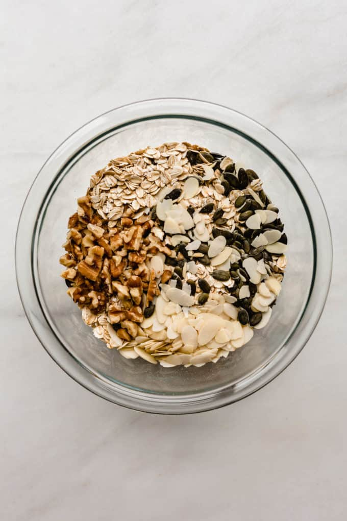 walnuts, almonds, pumpkin seeds and oats in a clear mixing bowl