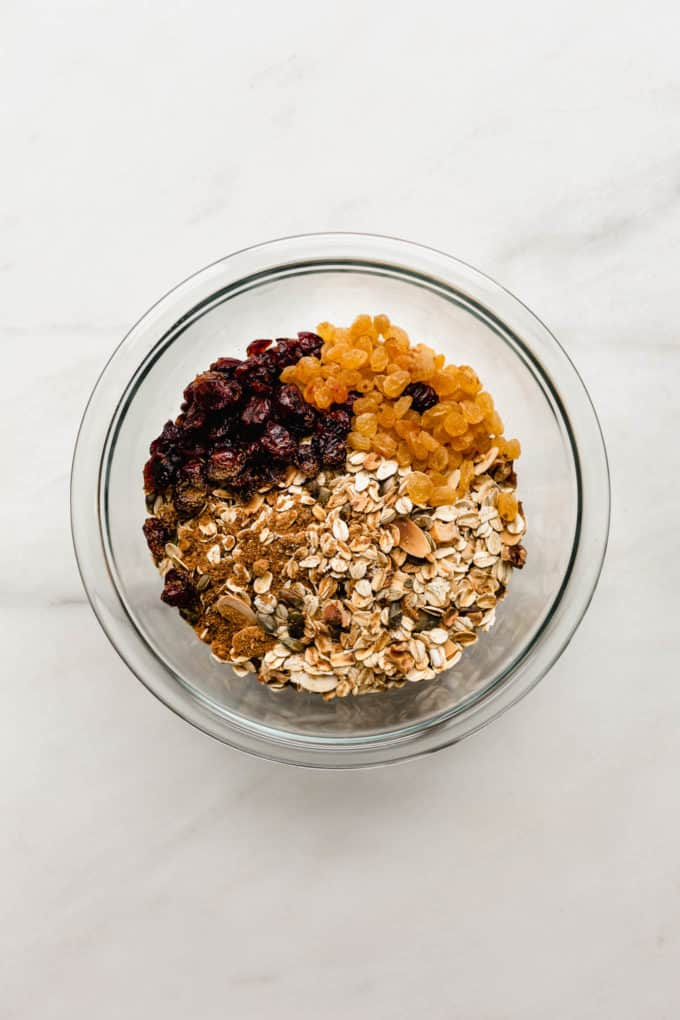 oats, nuts, dried cranberries and golden raisins in a clear mixing bowl