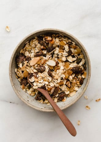 A bowl of muesli with a wooden spoon in it