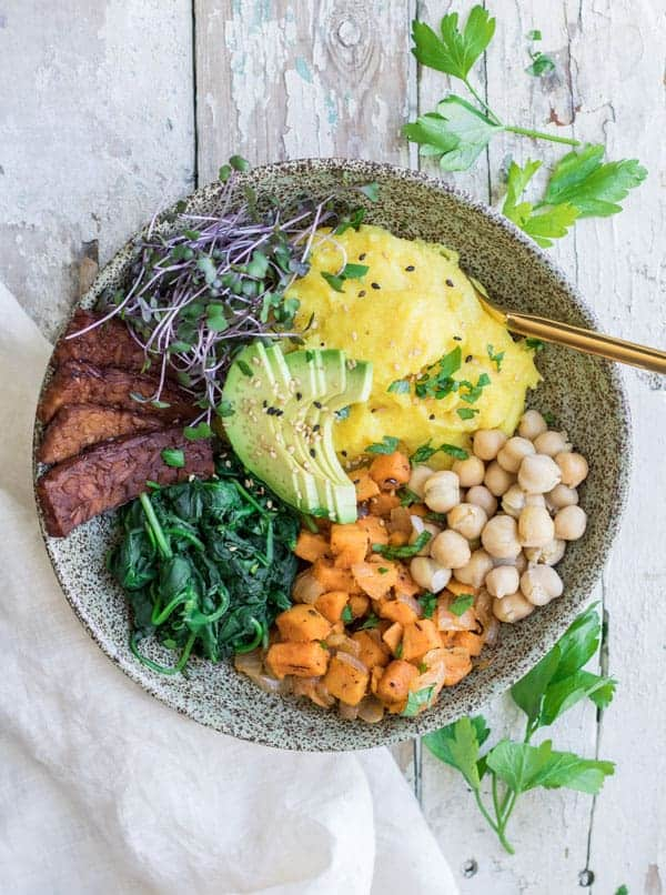 A breakfast bowl with polenta, tempeh and vegetables in it