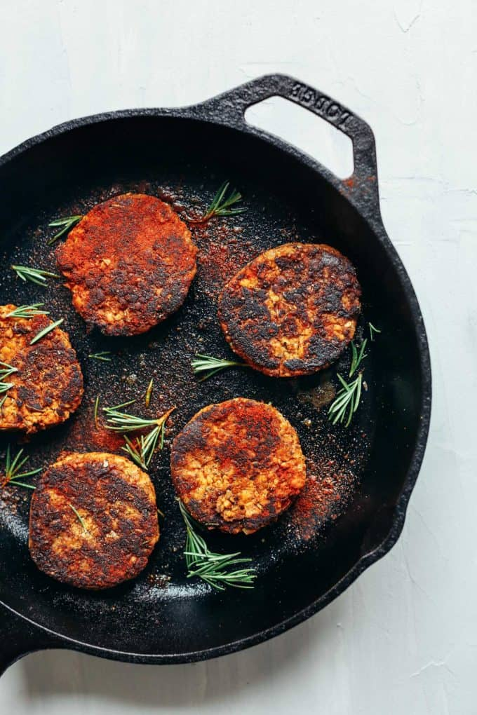 A cast iron skillet with tempeh patties in it