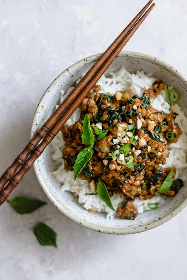 basil tempeh stir fry on rice in a light blue speckled bowl