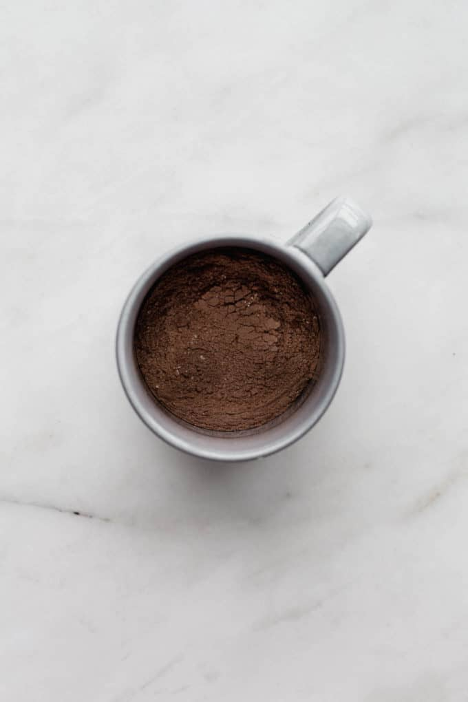 A grey mug with cocoa powder and flour in it
