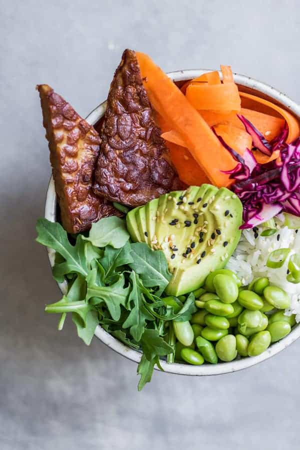 A bowl with vegetables, avocado and grilled tempeh in it