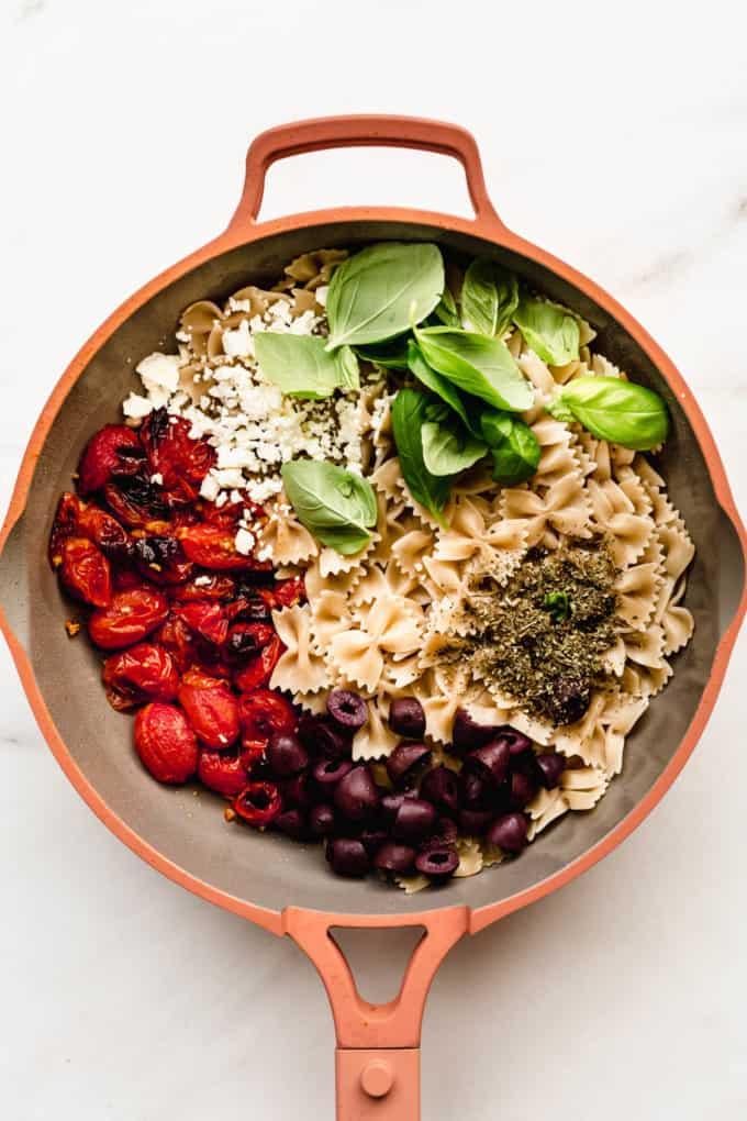 farfalle pasta, kalamata olives, roasted cherry tomatoes, feta cheese and basil in a pan