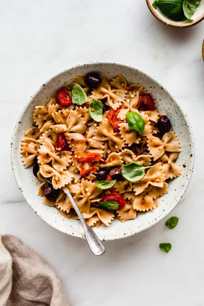 A bowl of mediterranean pasta topped with basil and a napkin on the side