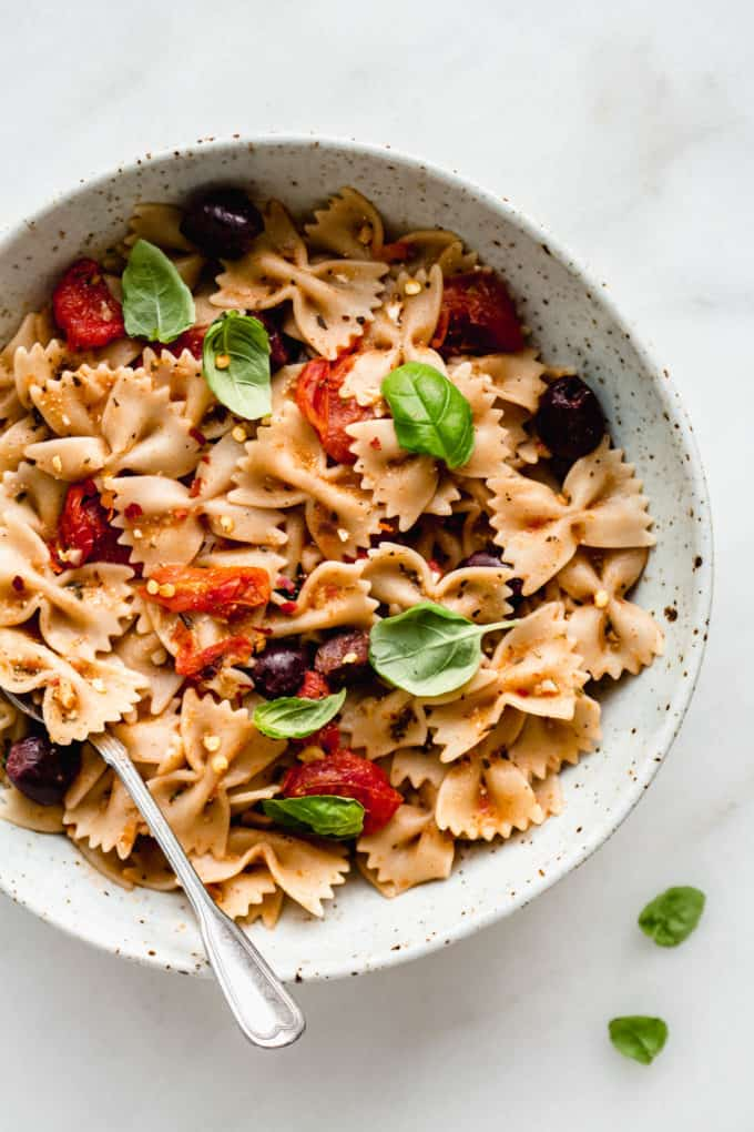 A bowl of farfalle pasta with olives, roasted tomatoes and basil